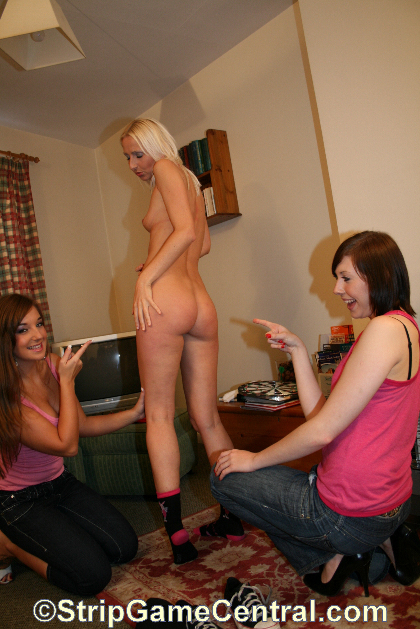 Two clothed women tease a naked woman