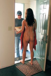 Woman accepting pizza delivery naked